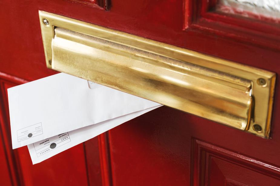 Envelopes poking out from a brass post box on a red door.